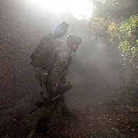 A soldier from 3 SCOTS (The Black Watch) shouts into a rising cloud of dust and smoke as he searches for casualties after an IED explosion just inside the doorway of a compound . Private Stephen Bainbridge, aged 25, from Kirkcaldy was gravely wounded in the blast which traumatically amputated his right leg and damaged his right so badly that it too later had to be amputated. His life was saved by the swift actions of Cpl John Goodie (21) a medic with 1 PWRR (The Princess of Wales's Royal Regiment) who applied tourniquets and first field dressings to get the bleeding under control. Private Chis Watson (21) also assisted in the treatment whilst reassuring the casualty and keeping him alert and responsive.  Once he had been stabilized the men CASEVAC'd Private Bainbridge to the MERT helicopter and he was rushed to Bastion Field Hospital.  Loya Manda, Nad e Ali, Helmand Province, Afghanistan on the 11th of November 2011.
