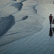 Couple walking at sunset on the beach.<br /> Santa Barbara, CA.