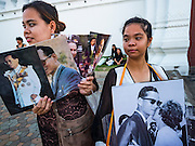 15 OCTOBER 2016 - BANGKOK, THAILAND:  Girls selling portraits of Bhumibol Adulyadej, the King of Thailand, on a street in front of the Grand Palace in Bangkok. King Bhumibol Adulyadej died Oct. 13, 2016. He was 88. His death comes after a period of failing health. With the king's death, the world's longest-reigning monarch is Queen Elizabeth II, who ascended to the British throne in 1952. Bhumibol Adulyadej, was born in Cambridge, MA, on 5 December 1927. He was the ninth monarch of Thailand from the Chakri Dynasty and is known as Rama IX. He became King on June 9, 1946 and served as King of Thailand for 70 years, 126 days. He was, at the time of his death, the world's longest-serving head of state and the longest-reigning monarch in Thai history.     PHOTO BY JACK KURTZ
