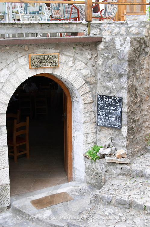 The entrance to a restaurant with the menu on a chalk board outside. Pocitelj historic Muslim and Christian village near Mostar. Federation Bosne i Hercegovine. Bosnia Herzegovina, Europe.