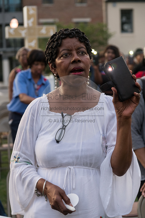 Relatives of the Emanuel 9, killed in a mass shooting at the historic Mother Emanuel African Methodist Episcopal Church, hold up flashlights during a candlelight vigil marking the 4th anniversary of the mass shooting June 19, 2019 in Charleston, South Carolina. Nine members of the historically black congregation were gunned down during bible study by a white supremacist on June 17, 2015.