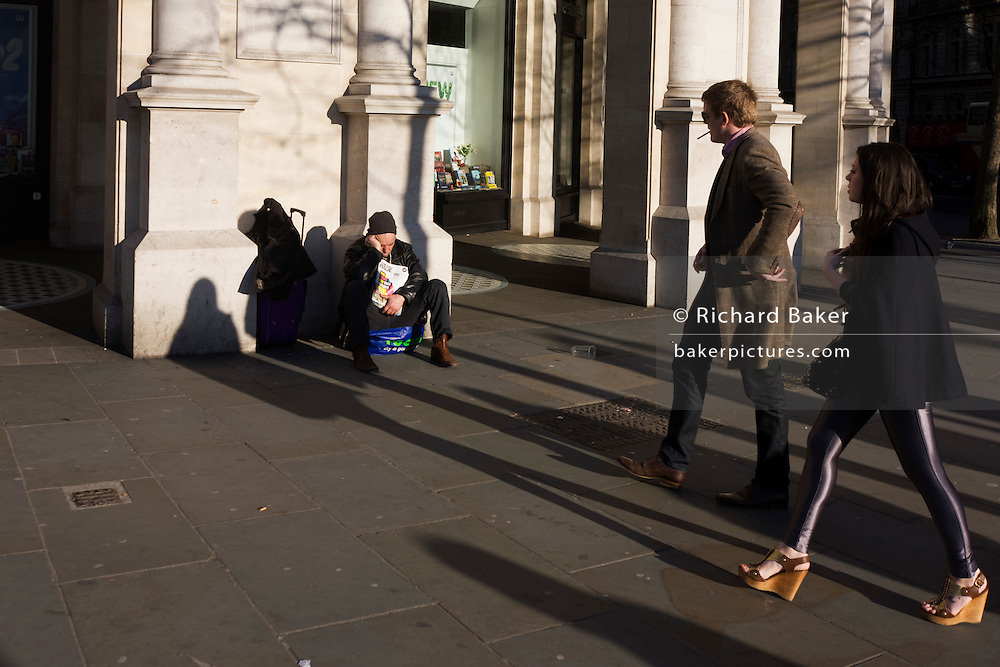 A sleeping Big Issue magazine seller sits alone without passing business as on-lookers pass disdainfully in London.