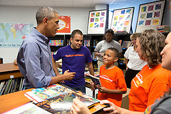 President Barack Obama speaks with volunteers working in the school library during a National Day of Service and Remembrance project at the Inspired Teaching Demonstration Public Charter School in Washington, D.C., Sept. 11, 2014. (Official White House Photo by Pete Souza)<br /> <br /> This official White House photograph is being made available only for publication by news organizations and/or for personal use printing by the subject(s) of the photograph. The photograph may not be manipulated in any way and may not be used in commercial or political materials, advertisements, emails, products, promotions that in any way suggests approval or endorsement of the President, the First Family, or the White House.