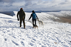 © Licensed to London News Pictures. 04/12/2020. <br /> Dog walkers on Penyfan, in the Brecon Beacons, the highest point in southern Wales and England, which has seen it's first snowfall of the year. Photo credit: Robert Melen/LNP