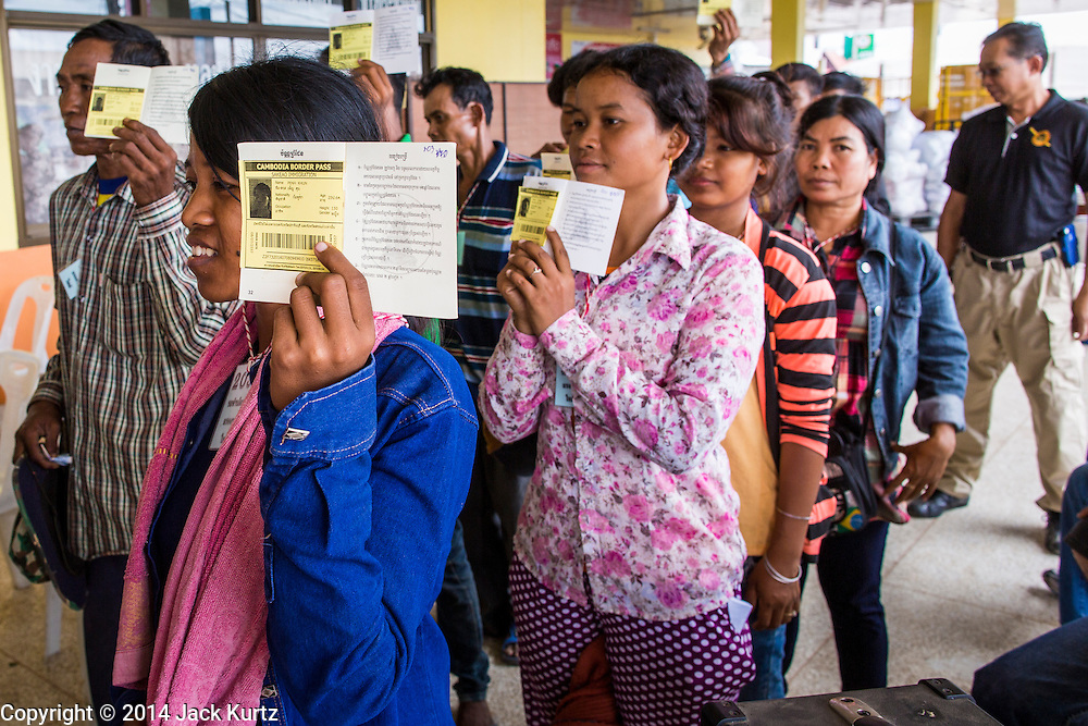 09 JULY 2014 - ARANYAPRATHET, SA KAEO, THAILAND:  Cambodian migrant workers hold up their border crossing permits as they file into  the Thai Immigration One Stop Service Center in Aranyaprathet on the Thai-Cambodian border. More than 200,000 Cambodian migrant workers, most undocumented, fled Thailand in early June fearing a crackdown by Thai authorities after a coup unseated the elected government. Employers have been unable to fill the vacancies created by the Cambodian exodus and the Thai government has allowed them to return. The Cambodian workers have to have a job and their employers have to vouch for them. The Thai government is issuing temporary ID cards to allow them to travel openly to their jobs. About 800 Cambodian workers came back to Thailand through the Aranyaprathet border crossing Wednesday. The Thai government has opening similar service centers at three other crossing points on the Thai-Cambodian border.   PHOTO BY JACK KURTZ