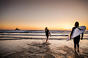 Surfers carrying their surfboards and running into the sea and surf, surrounded by the orange light of sunset at La Rocco Tower, St Ouen's Bay, Jersey, Channel Islands