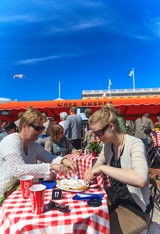 Tourists enjoying crepes at Helsinki Market Square in Finland.