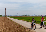 Children are cycling on a field road with view to the skyline of Frankfurt am Main in the back.