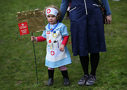 © Licensed to London News Pictures. 09/01/2016. London, UK. Two year old Annabel Pickstone holds a placard as she stands with her mother Senior Sister Nicola Pickstone during a rally against the proposed cancellation of bursaries for nurses hoping to train for work in the NHS.  Photo credit: Peter Macdiarmid/LNP
