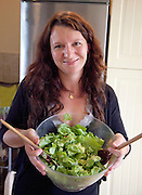 Happy Polish woman age 32 holding a glass salad bowel of fresh greens in her kitchen. Zawady Central Poland