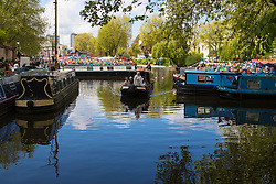 Little Venice, London, May 3rd 2015. After a dull, damp start to the day, hundreds of Londoners and narrowboat enthusiasts arrive at Paddington Basin at the juction of the Regents and the Grand Union Canals for the annual Inland Waterways Association's Canalway Cavalcade, celebrating the history and traditions of Britains vast network of canals and navigable rivers. PICTURED: Traveling through the moored fleet, The Blessing of the Boats is a rite proudly undertaken by Father Gary Bradley, Vicar of Little Venice.