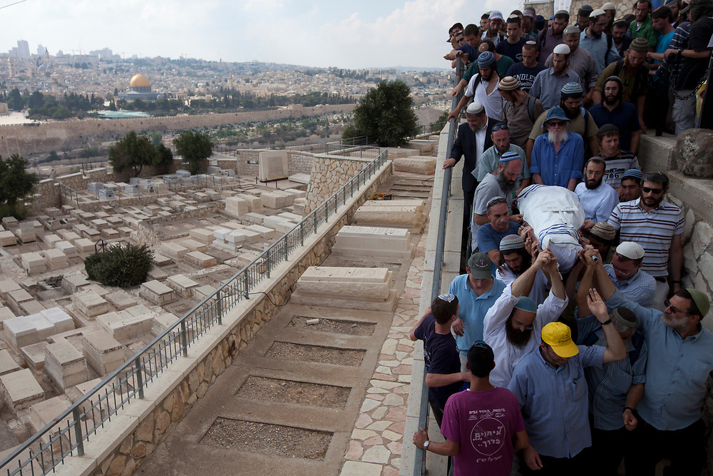 The Dome of the Rock and Jerusalem's Old City are seen to the left as mourners carry the body of Yitzhak Imes who was killed in a shooting attack near the West Bank city of Hebron, during the funeral procession for him and his wife Talia in Jerusalem's Mount of Olives cemetery, on September 1, 2010. Four Israelis were killed in a Palestinian shooting attack last night when they drove through the West Bank, Islamist Palestinian group Hamas claimed responsibility for the attack.