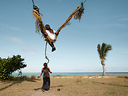 Bajau kids playing on swing attached to coconut tree on Mantabuan island.