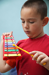 Boy playing with a toy xylophone,