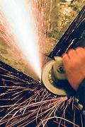 Alaska. Using a grinder on steel throwing sparks.