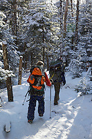 Two boys hiking in the snow.