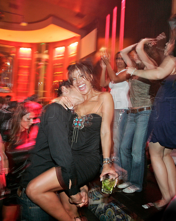"""Alexis Josif hugs Mirela Gonzalez as they celebratte the 20th anniversary of South Beach """"SOBE"""" and ten years after the death of Gianni Versace at SET Night Club on Miami Beach,"""