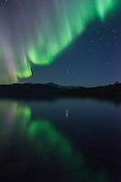 Northern lights reflect in lake Sitojaure outside of Sitojaure hut, Kungsleden trail, Lapland, Sweden