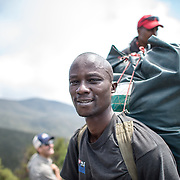 A porter carrying his load in the heath zone on Mt Kilimanjaro's Lemosho Trail at about 10,000 feet.