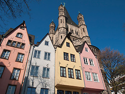 Gross St Martin Church and historic coloured houses in FischMarkt or Fish Market in Cologne Germany