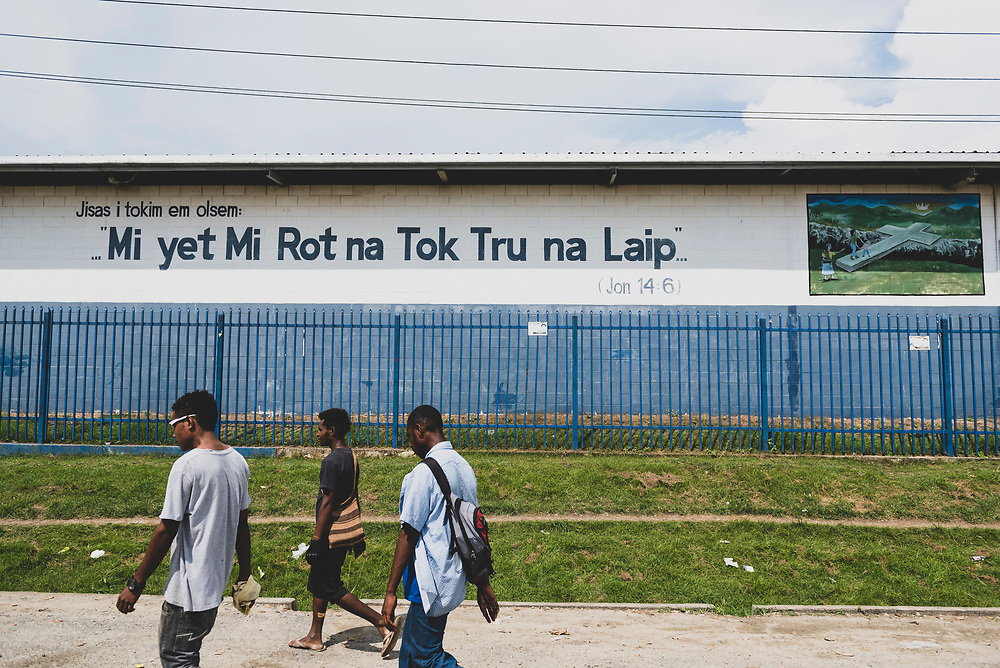 """People walk past a building on which is painted a Bible verse, John 14:6, in Melanesian Pidgin (Tok Pisin). It reads, """"Mi yet Mi Rot na Tok Tru na Laip."""" (July 21, 2017)"""