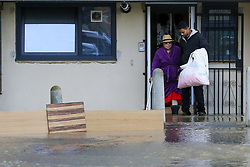 © Licensed to London News Pictures. 08/10/2019. London, UK. An elderly resident is assisted to moved out of the flat,  following a burst water main on Brownswood Road in Finsbury Park, north London, causing flooding in a housing estate. Emergency services and Thames Water are at the scene.  Photo credit: Dinendra Haria/LNP