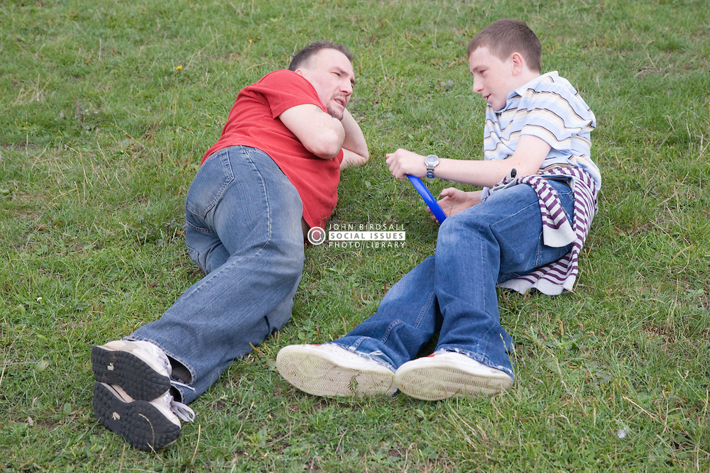 Father and son lying on the grass talking,