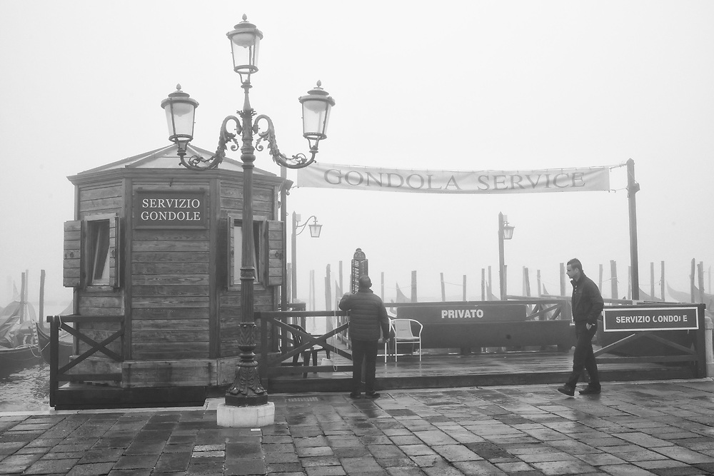 A gondolier checks his shift for the day  while Venice wakes up un in a cloud of fog