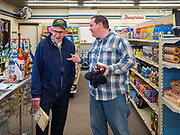 "25 FEBRUARY 2020 - BUTTERFIELD, MINNESOTA: DAVID LINSCHEID (left) and TIM HALL chat in the True Value Hardware Store in Butterfield, MN, a farming community of about 500 people 130 miles southwest of the Twin Cities. The town has been a ""food desert"" for 10 years after its only grocery store closed in 2010. Linscheid's family opened the previous grocery store in town in 1905 and was forced to close it in 2010. Now Lincheid shops at the True Value. Barb Mathistad Warner and Mark Warner purchased the True Value store in Butterfield in December, 2018 and started selling groceries in the store in May, 2019. For residents of Butterfield going to a grocery store meant driving 10 miles to St. James, MN, or 20 miles to Windom, MN, the two nearest communities with grocery stores. The USDA defines rural food deserts as having at least 500 people in a census tract living 10 miles from a large grocery store or supermarket. There is a convenience store in Butterfield, but it sells mostly heavily processed, unhealthy snack foods that are high in fat, sugar, and salt.    PHOTO BY JACK KURTZ"