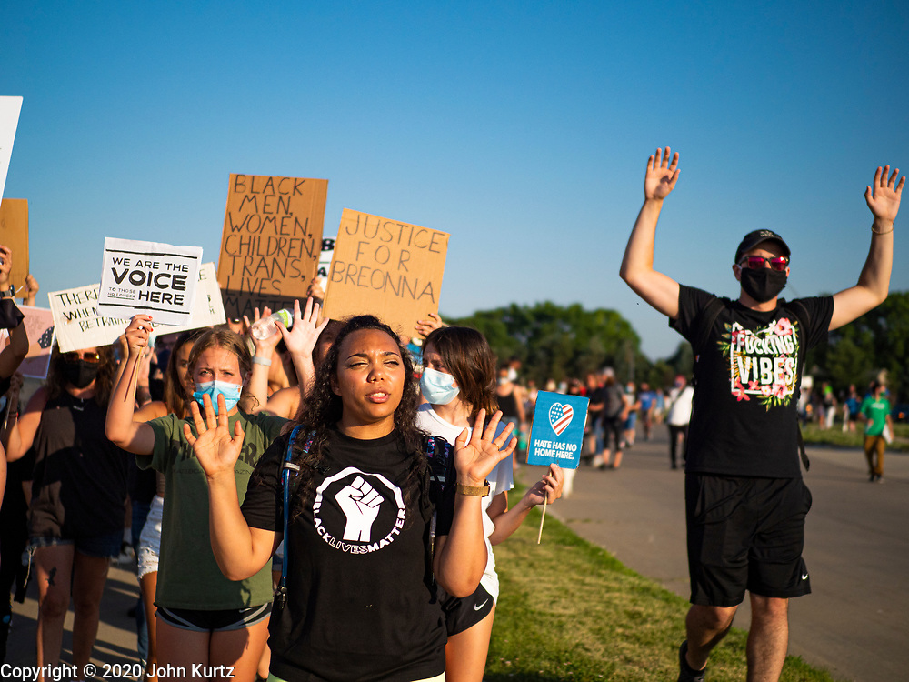 "17 JUNE 2020 - NORWALK, IOWA: Supporters of Black Lives Matter hold up their hands and chant ""hands up, don't shoot"" during a march in Norwalk. About 400 supporters of Black Lives Matter marched through Norwalk, IA, an upper class suburb of Des Moines Wednesday. Norwalk has a population of about 10,000 and, according to the US Census Bureau, is 97 percent white. The marchers were protesting police violence against people of color. The march was a reaction to the police killing of George Floyd in Minneapolis in May. The march was peaceful.        PHOTO BY JACK KURTZ"