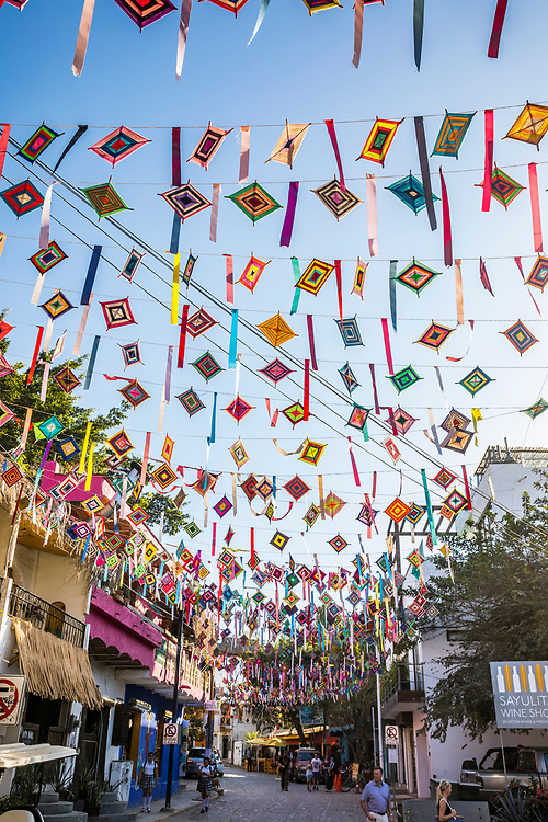 """Ojos de Dios or """"God's Eye"""", a local symbol and craft of the indigenous Huichol culture hang from wires above the streets of Sayulita, Nayarit, Mexico."""