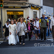 Crossing roads, many locals position themselves in the first row to avoid being obstructed by the tourists. On their way to the First Communion celebration. Sagrada Família area.