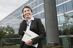 Attractive businesswoman speak a cell phone standing in front of a modern office building, Bavaria, Germany