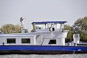 Nederland, Schoonhoven, 16-5-2018Binnenvaartschip, vaart over de Lek. Man en vrouw, echtpaar, zit in de stuurhut . Man als kapitein aan het roer .Foto: Flip Franssen