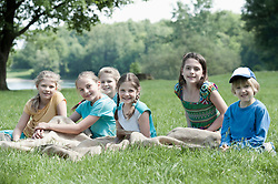 Group of children sitting on meadow and have a rest after sack race, Munich, Bavaria, Germany