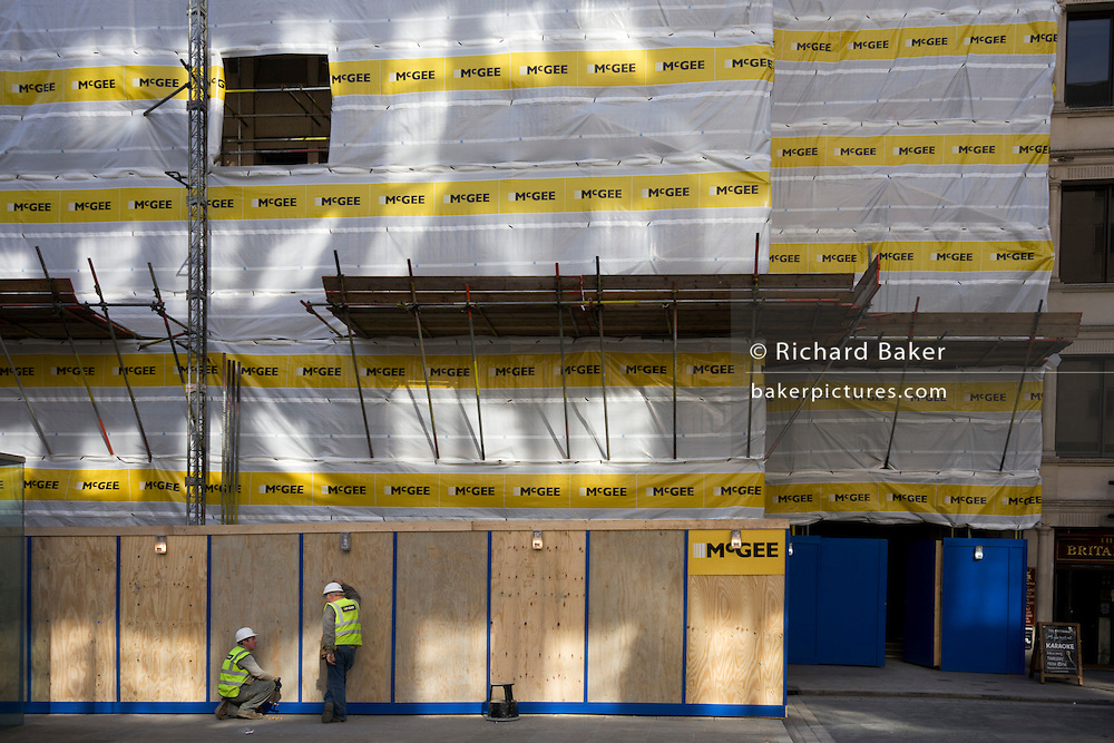 EMployees of construction contractor McGee talk beneath company sheeting and scaffolding in London's square mile.
