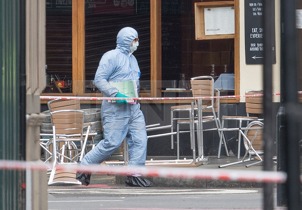 © Licensed to London News Pictures. 05/06/2017. London, UK. A police forensic officer passes overturned chairs at the Brindisa cafe in Borough Market as investigations continue following a terrorist attack on Saturday evening. Three men attacked members of the public  after a white van rammed pedestrians on London Bridge.   Ten people including the three suspected attackers were killed and 48 injured in the attack. Photo credit: Peter Macdiarmid/LNP