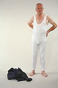 Elderly man in his underwear waiting against a white backdrop