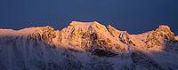 Winter sunset illuminates snow covered mountain peaks, Flakstadøy, Lofoten Islands, Norway