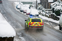 Monday January 21 - A vehicle from South Yorkshire Ambulance Service with blue lights flashing makes its way down Church Street through the winter weather in  Ecclesfield, Sheffield with the promise of more to follow.21 January 2013.Image © Paul David Drabble