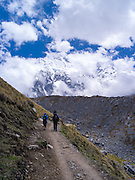 Hiking on the Camino Salkantary, with Montaña Salkantay and its glacier in the background, near Soraypampa, Peru.