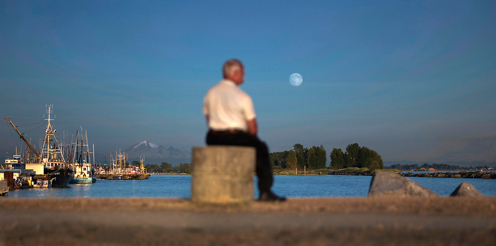 The annual super moon rises over the Fraser River at sunset in Richmond, British Columbia. (2014)