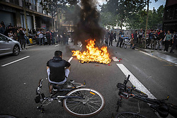May 26, 2019 - Barcelona, Catalonia, Spain - A Glovo delivery boy, seated on his bike, watches the fire in front of Glovo company headquarters as a group of couriers burned their delivery packs protesting poor working conditions after a traffic accident death of a fellow delivery worker who was hit by a municipal cleaning services truck. Glovo is a Spanish food-on-demand start-up founded in Barcelona in 2015, and operating in 24 countries. (Credit Image: © Paco Freire/SOPA Images via ZUMA Wire)