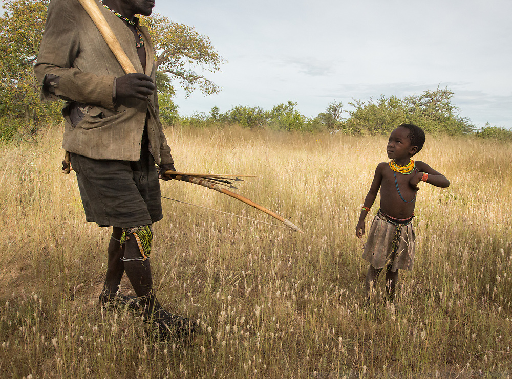 Hunter and young Hadza girl going in the savannah. At the Hadza camp of Senkele.