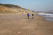 Two people walking on beach. Dunwich beach and cliffs, North Sea coast, Suffolk, East Anglia, England.  Rapidly eroding soft sandy cliffs illustrate how Dunwich, at one time one of the largest towns in England was lost to the sea.