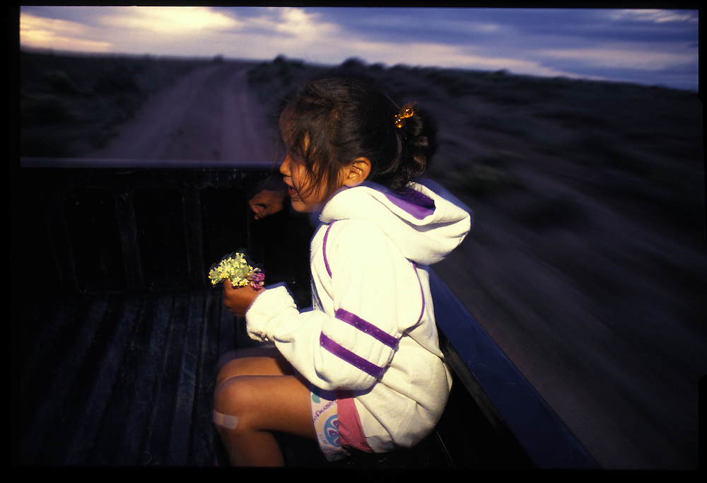 """Desiree Taleman (6) rides home in the back of a truck after picking flowers for her mom.  There is increasing proof that yonf navajos can not only cope, but succeed.  """"Our kids are learning that they can compete  against non-indian kids and be better than them,"""" tribal President Peterson Zah says.  """"That's a very important lesson."""""""