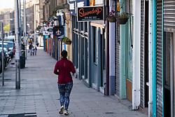 Edinburgh, Scotland, UK. 1 May 2020. Views of Edinburgh as coronavirus lockdown continues in Scotland. Streets remain deserted and shops and restaurants closed and many boarded up. Pictured; Female jogger runs along Leith Walk with most shops and restaurants closed and shuttered. Iain Masterton/Alamy Live News