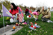 Angel Dahlke, 2, of Pasco, hugs her grandmother Masako Jackson's arm while her mother, Patricia Dahlke, both of Pasco, and uncle, John Jackson of Tacoma, visit Donald Jackson's grave at City View Cemetary in Pasco. Donald Jackson, a First Class Petty Officer in the Navy, who served in Korea and Vietnam, passed away in March. His wife, Masako, and daughter, Patricia, have been visiting the site every five days since then. For Memorial Day, siblings Patricia and John, a retired lieutennant commander in the Navy Reserves, brought extra flags for the other veterans' plots at City View to ensure nobody was forgotten.
