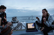 North Atlantic Ocean, September 2014.<br /> Marine biologist Stephanie Wright gives a lecture on microplastic on board the Sea Dragon while a dolphin jumping in the background distracts the audience! © Chiara Marina Grioni