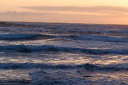 Waves crashing onto beach at sunset, Hug Point State Recreation Area, Oregon, USA